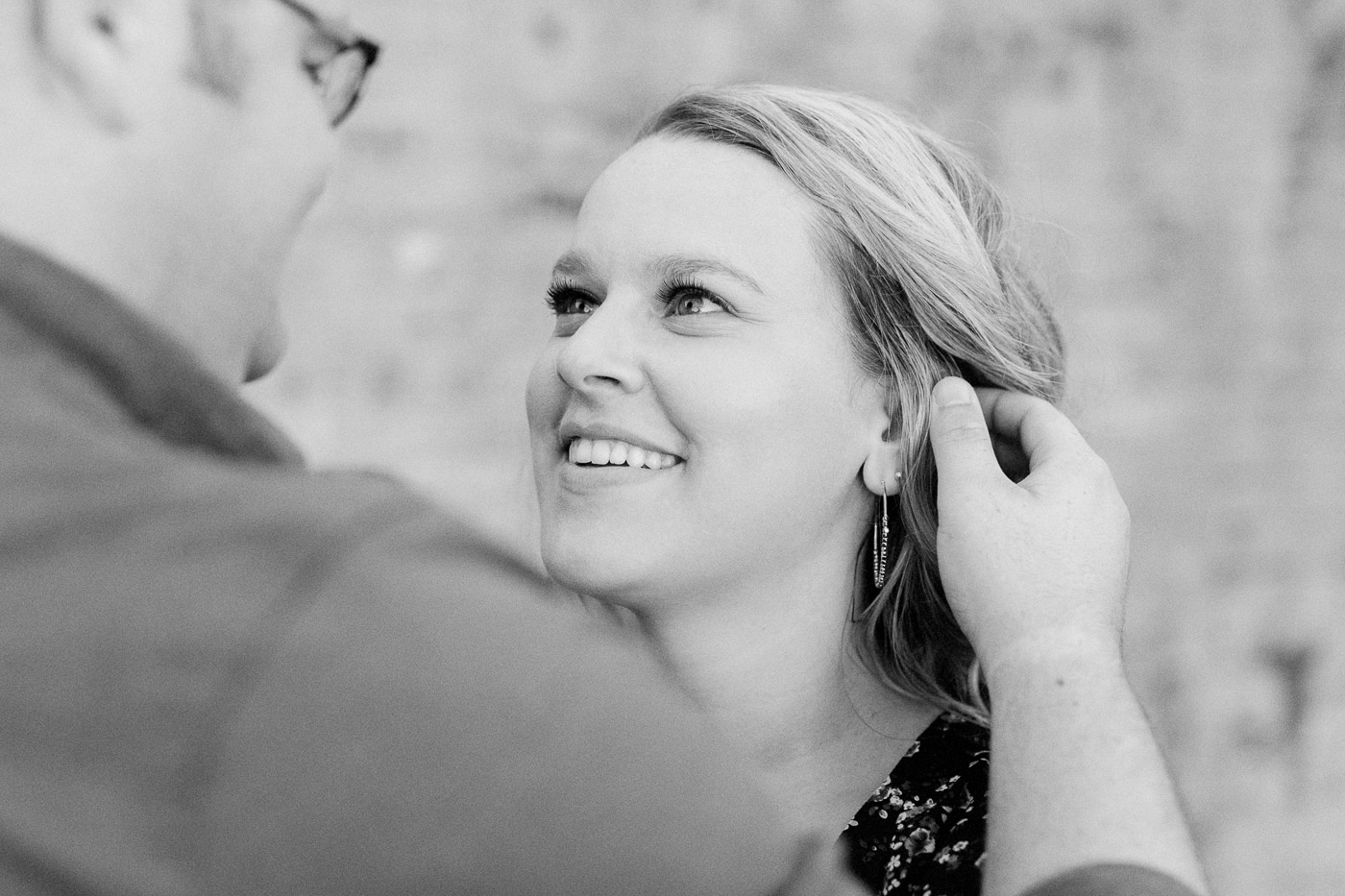 Andrew is touching Jaymee's hair during their Huntington beach state park engagement session