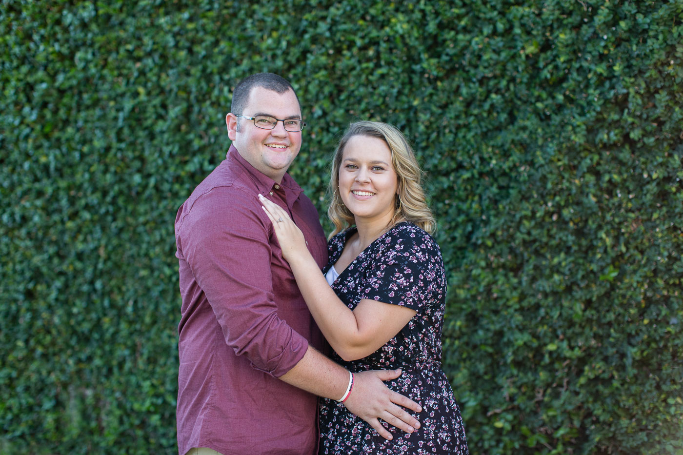 Andrew and Jaymee posing in front of a beautiful green wall during their Huntington beach state park engagement session
