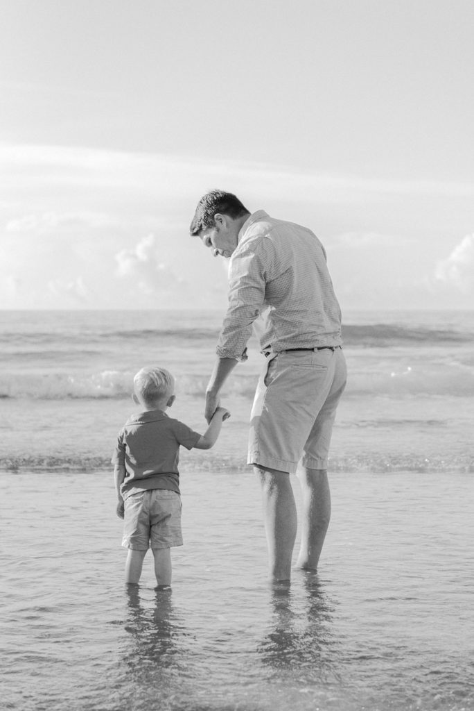Happy Father Holding Hand Of Little Son While Walking Together On The Beach