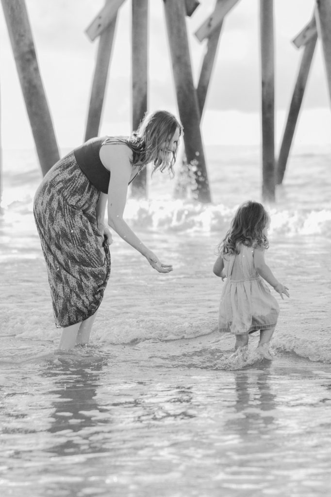 Mother playing with her daughter in the waves