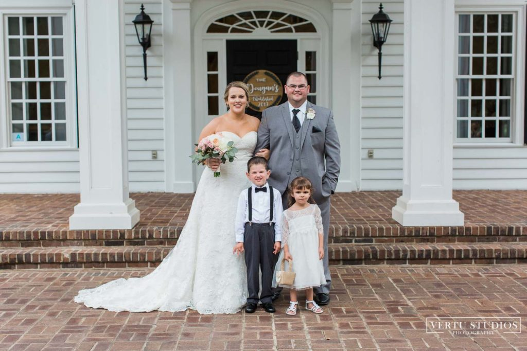 bride and groom posing with the flower girl and ring bearer